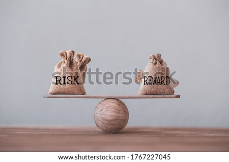 Risk and reward bags on a basic balance scale in equal position on wood table. risk management concept, depicts investors use a risk reward ratio to compare the expected return of an investment Royalty-Free Stock Photo #1767227045