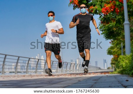 Morning run, a man with medical mask runs along the road with a beautiful view of Dubai. UAE, fitness, sport, exercising and healthy lifestyle concept. #1767245630