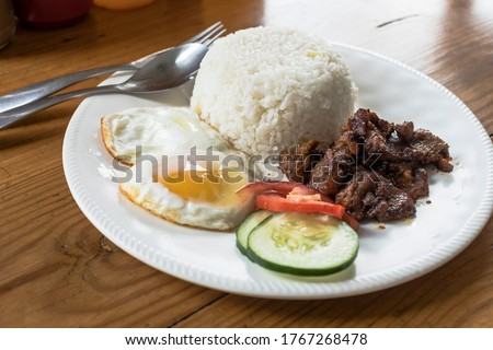 Tosilog (Tocilog): Filipino Breakfast composed of Tocino (cured meat), garlic rice (sinangag) and egg. with cucumber and tomato garnish.