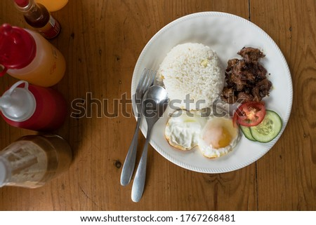 Tosilog (Tocilog): Filipino Breakfast composed of Tocino (cured meat), garlic rice (sinangag) and egg. with cucumber and tomato garnish. Top view.