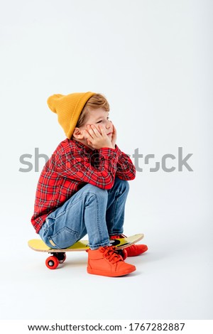 tired child is sitting on a skateboard, dressed in red shirt with squares and jeans, isolated on white background, studio shot