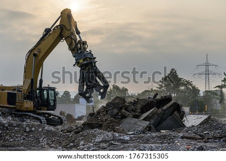 Building House Demolition site Excavator with hydraulic crasher machine and yellow container Royalty-Free Stock Photo #1767315305