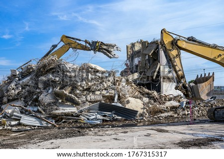 Building House Demolition site Excavator with hydraulic crasher machine and yellow container Royalty-Free Stock Photo #1767315317