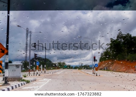 Blurry pictures of the streets and rainstorms that are forming above the sky while driving make it a cautious drive. The concept of being more cautious when driving on the road during the rainy season