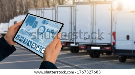 Manager with a digital tablet on the background of trucks. Fleet management #1767327683