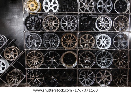 wall of alloy wheels in the store. Auto repair shop background. Auto Wheel Service Royalty-Free Stock Photo #1767371168