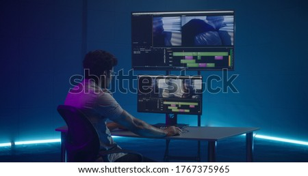 Medium shot of video editor working at his workstation