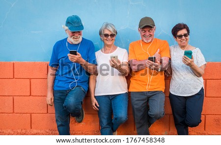 Two couples of brothers and wifes looking at smart phone smiling against a colored wall - four happy people using tech and social - active retirement concept