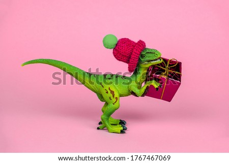 cute green plastic toy dinosaur wearing knitted hat and holding present box  pink background