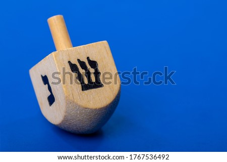 Dreidel or dreydl on blue background