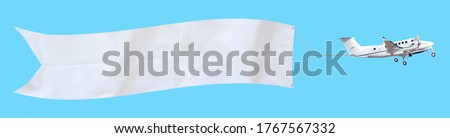 Propeller aircraft with a long white advertising banner made of fabric. Isolated on a blue background
