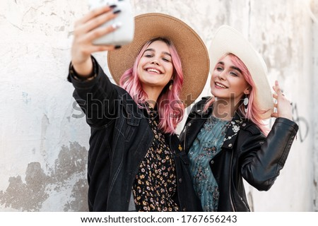 Two positive young women with pink hair in fashionable clothes in straw elegant hats take selfie on modern photo camera near white wall on street. Happy girls smiling and taking pictures themselves.