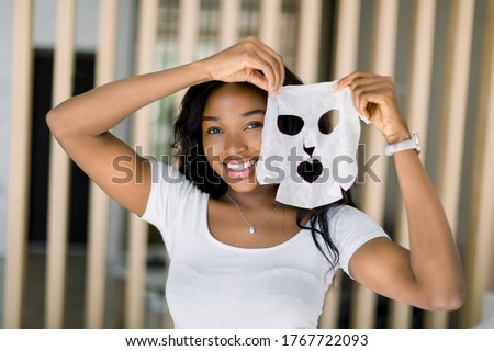 Beautiful young African American lady in white t-shirt, enjoying her beauty procedures at home, going to apply a white face sheet mask on face. Spa procedures at home Royalty-Free Stock Photo #1767722093