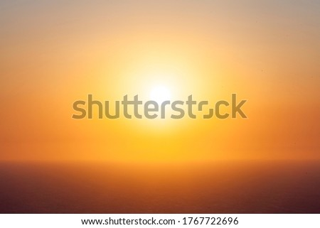 The sunset over the sea the sun fills with light all around all merged a large yellow spot