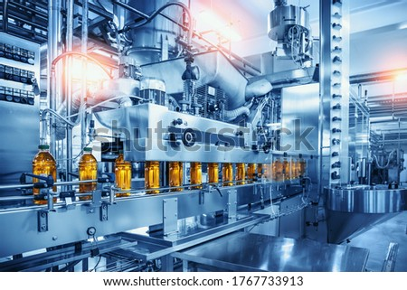 Conveyor belt with juice bottles on beverage factory interior in blue color. Royalty-Free Stock Photo #1767733913
