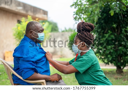 image of an aged African man being checking up by a health worker-young black nurse wearing a face mask taking care of an old man- health worker at home service #1767755399