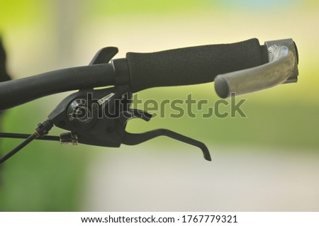 old handlebar bike, brake lever, and gear changer, bar end, foam handle and blurred green background