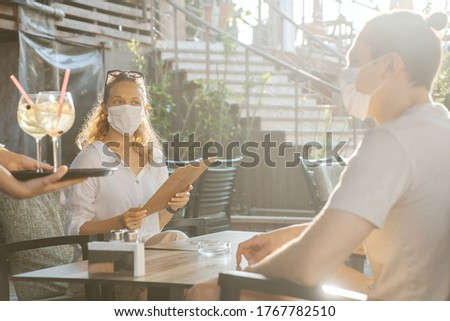 Couple with medical facemask are keeping social distance in restaurant. Aftermath of covid-19 relief of Quarantine measures Royalty-Free Stock Photo #1767782510