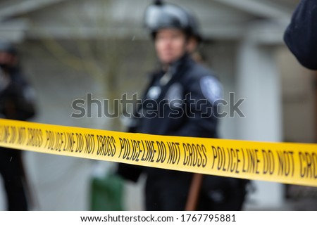 """""""Police Line Do No Cross"""" caution tape, with a law enforcement officer in the blurry background Royalty-Free Stock Photo #1767795881"""