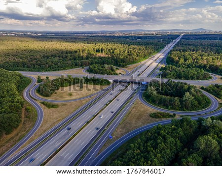 The highway intersection of the highway 5 between Frankfurt and Darmstadt in Germany at a cloudy and windy day in summer. Royalty-Free Stock Photo #1767846017