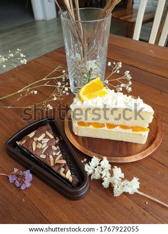 Picture of Orange cake and brownie cake on the dry flower background on the wooden table.