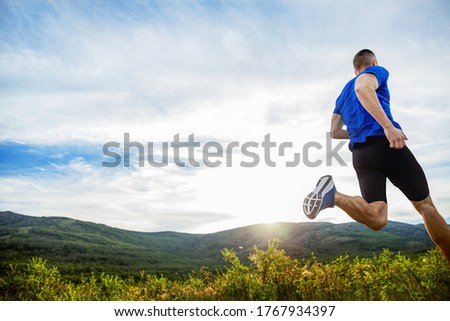 back athlete runner run mountain meadow in rays of sunset