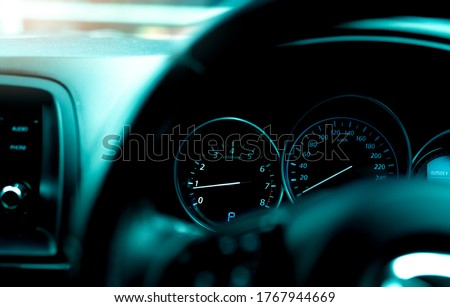 Car dashboard interior view. Car instrument panel with tachometer and speedometer. View from steering wheel to rpm gauge and speed meter. Car engine indicator. Closeup dashboard with auto light. #1767944669