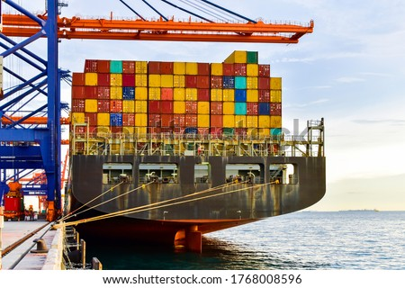 Huge panamax size container vessel discharging and loading container cargo at port terminal. Quay crane pick up container from truck onto ship. #1768008596