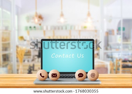 Call Center and Contact US Concept : Contact icons symbol put on laptop with blurry image of coffee cafe in background.