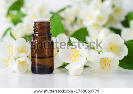 Small glass bottle with essential jasmine oil (tincture, infusion, perfume) on the white background. Jasmine flowers close up. Aromatherapy, spa and herbal medicine ingredients. Copy space.  #1768060799