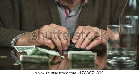 retired man holds hands on black wallet sitting at table reflecting banknotes cognac bottle and empty glass close view Royalty-Free Stock Photo #1768071809