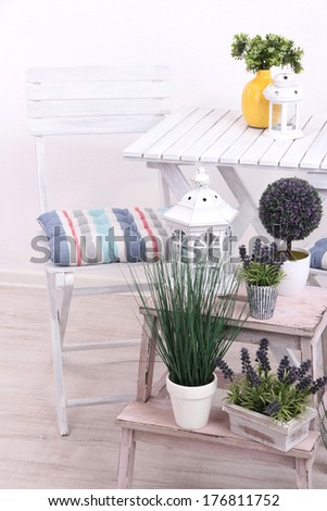 Garden chair and table with flowers on wooden stand on white background #176811752