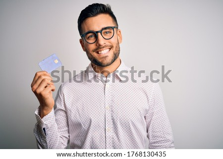 Young business man holding credit card over isolated background with a happy face standing and smiling with a confident smile showing teeth