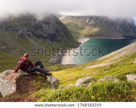 Lofoten, Norway - August; Tourist with a backpack on the trail to Ryten from the Kvalvika Beach,  Lofoten, Northern Norway. Northern Europe. Scandinavia.