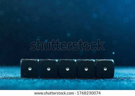 Game cubes are next to each other. Five identical black cubes on blue background. Photo with bokeh.