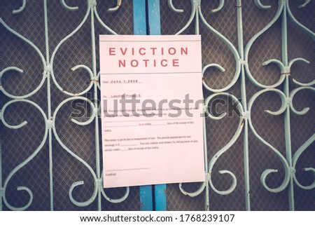 Foreclosed or eviction notice on a main door with blurred details of a house with vintage filter Royalty-Free Stock Photo #1768239107