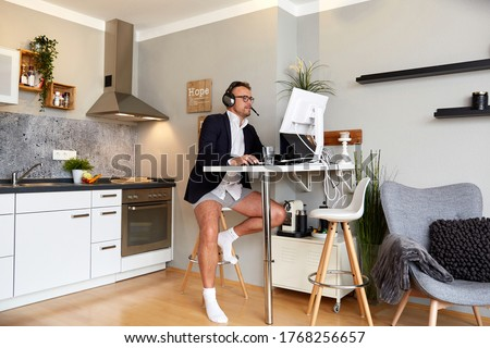 Handsome businessman wearing suit and underwear while on video call at home