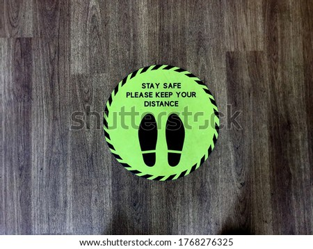 A round green floor sign says 'Stay Safe please keep your distance'. It has two footprints on it indicating where to stand.Image