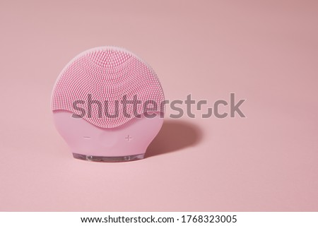 Silicone electric facial cleanser brush for skin care on pink background