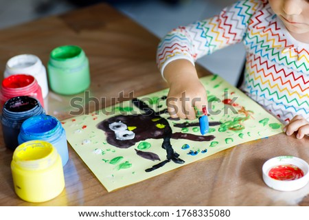 Closeup of little creative toddler girl painting with finger colors an owl bird. Child having fun with drawing at home, in kindergarten or preschool daycare. Games, education and distance learning for