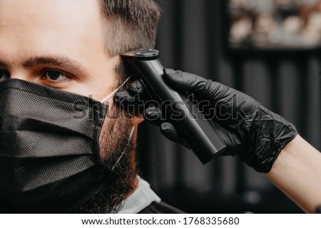 Woman barber cutting hair to a bearded man in face mask. Quarantine haircut concept. Royalty-Free Stock Photo #1768335680