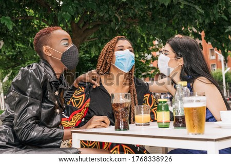 three multiracial, black, mixed raze and Caucasian friends on a bar terrace drinking a drink while having fun with face masks due to the coronavirus covid 19 pandemic #1768338926