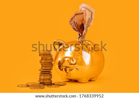 Golden piggy bank with money tower and dollar bills on yellow background. Stack of euro coins near golden money box. Moneypig, money saving, moneybox, finance and investments concept.