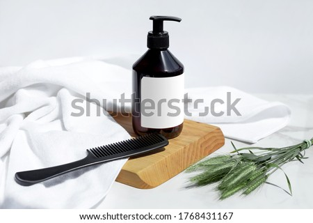 Bottle of shampoo, conditioner or hair mask with white towel, hairbrush, wood and herbs on a white background. Organic cosmetic. Treatment spa beauty skincare healthcare. Brand commercial. Product Royalty-Free Stock Photo #1768431167