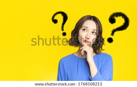 Young woman with question marks. Royalty-Free Stock Photo #1768508213