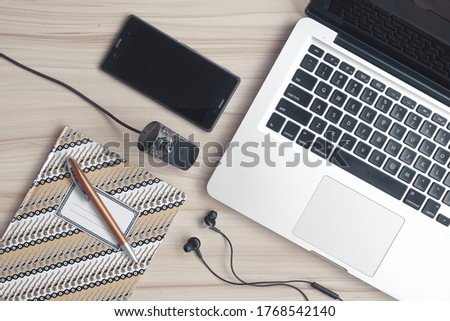 Home office workplace with laptop, external webcam and smartphone in top view on a wooden table. A concept of work from home in new normal era based on connectivity through internet and online meeting Royalty-Free Stock Photo #1768542140