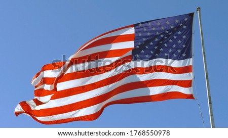 American flag on a blue sky background. USA flag flaping in wind. Close-up of an American flag flying in the wind against a background of clear sky. Close up of American flag waving. American concept. #1768550978