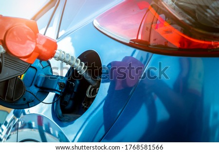 Car fueling at gas station. Refuel fill up with petrol gasoline. Petrol pump filling fuel nozzle in fuel tank of car at gas station. Petrol industry and service. Petrol price and oil crisis concept. #1768581566