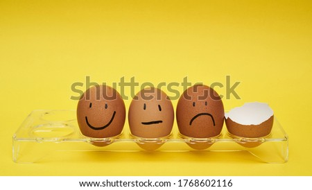 Chicken eggs in an egg holder. Full tray of eggs. Half an egg, egg yolk, shell. Emotion and facial expression painted on eggs #1768602116