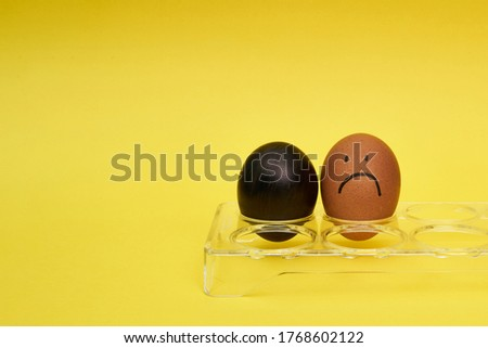 Chicken eggs in an egg holder. Full tray of eggs. Half an egg, egg yolk, shell. Emotion and facial expression painted on eggs #1768602122
